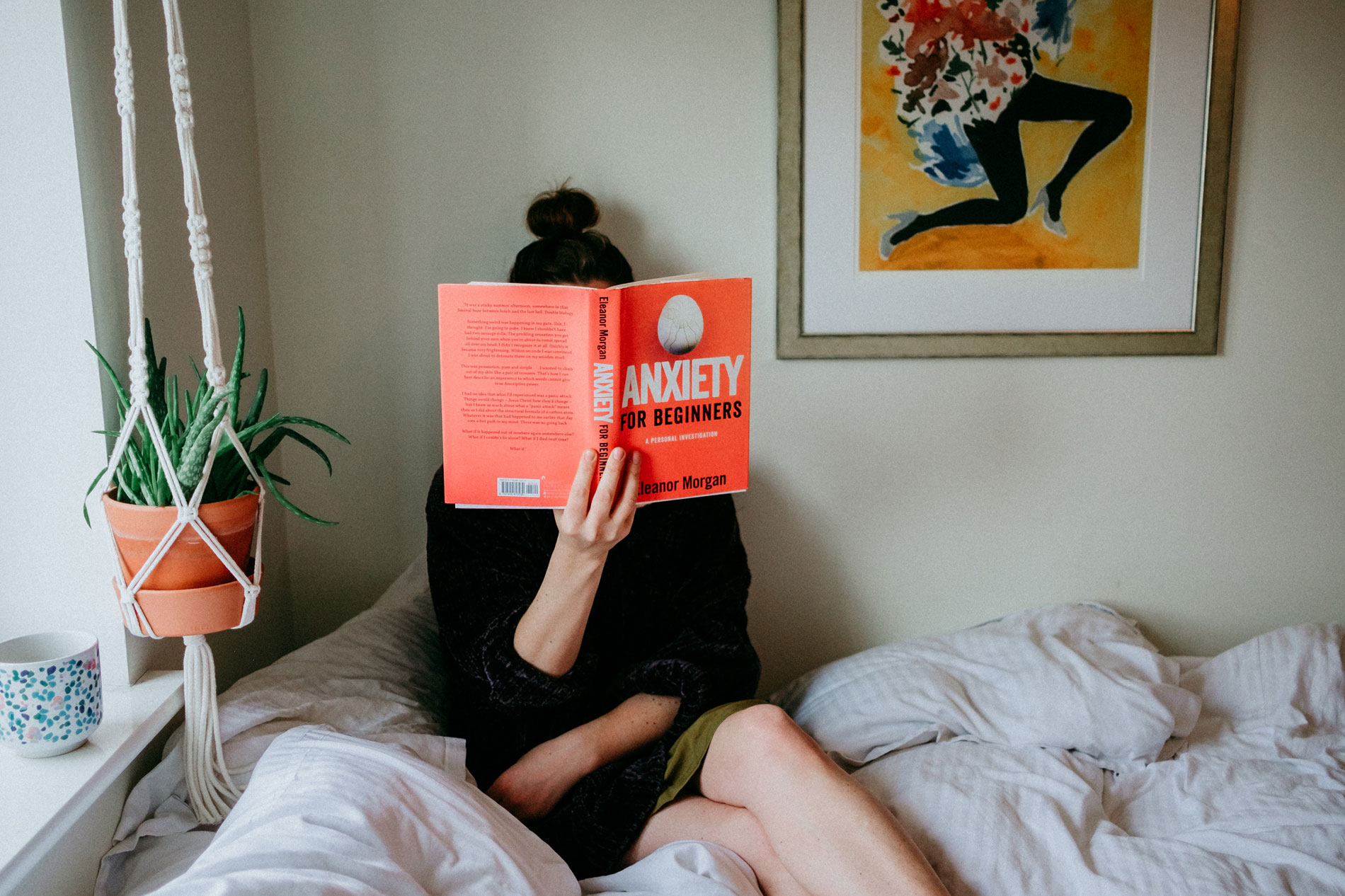 woman sitting on a bed reading a self help self-care book next to coffee and hanging plant