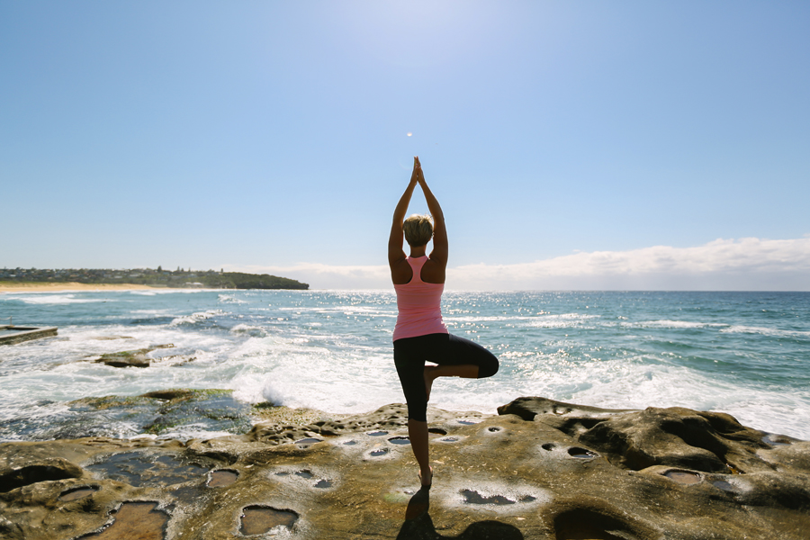 woman doing yoga tree pose on the beach