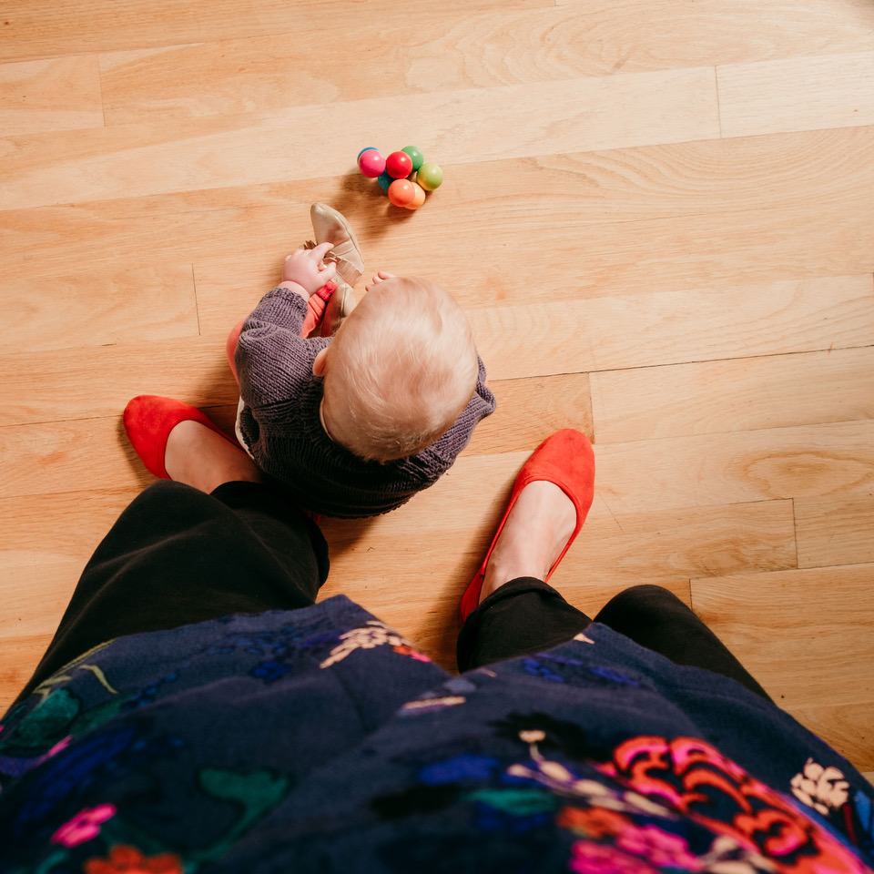 baby sitting and playing by stylish mother's feet on wooden floor