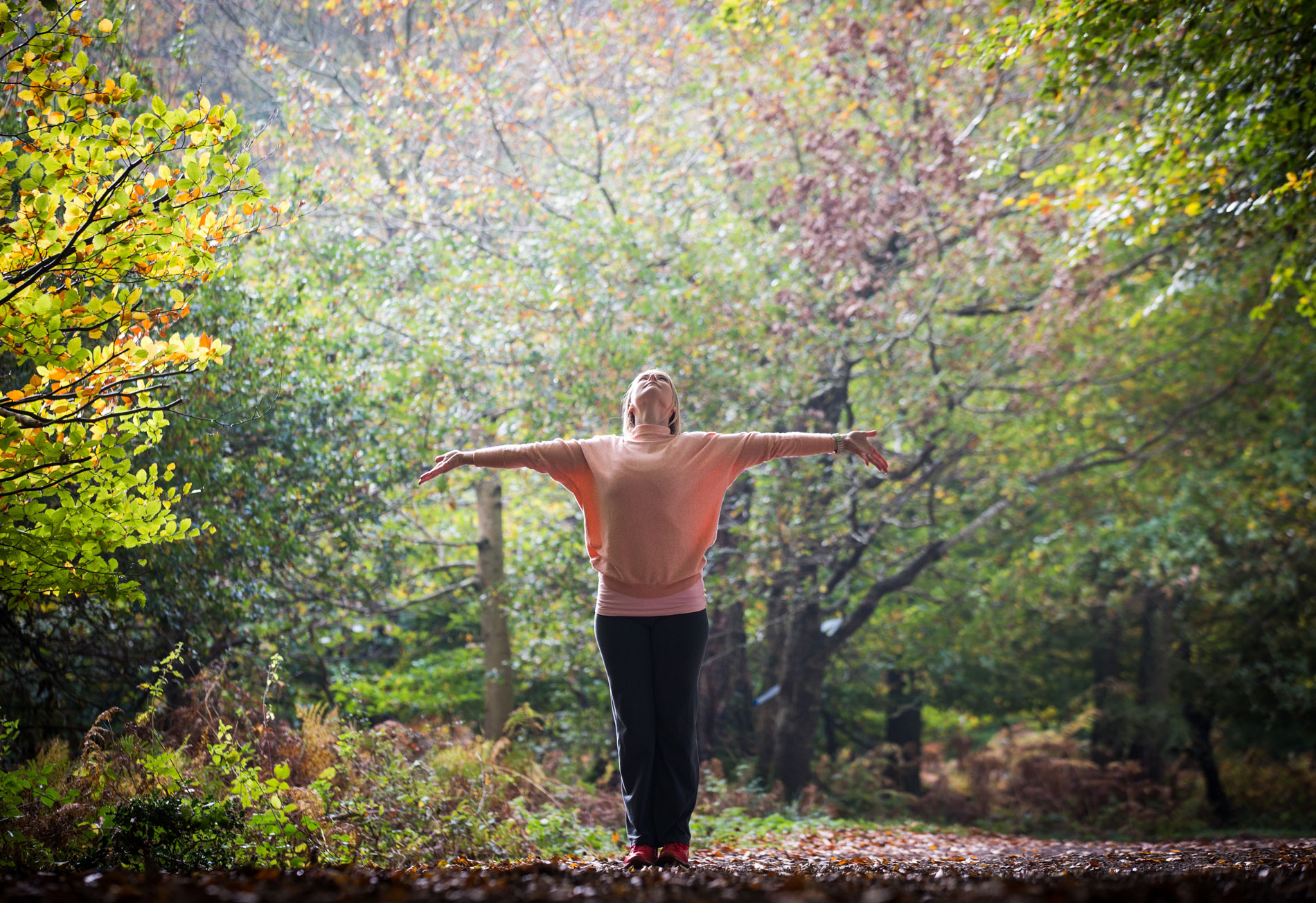 woman doing yoga mountain pose in forest
