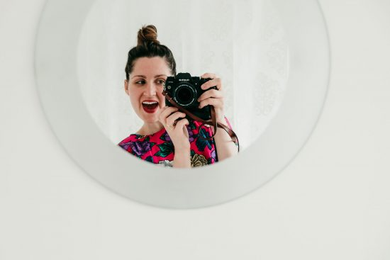 woman wearing lipstick and bright, pink, colourful flowered top is taking a selfie in a mirror.