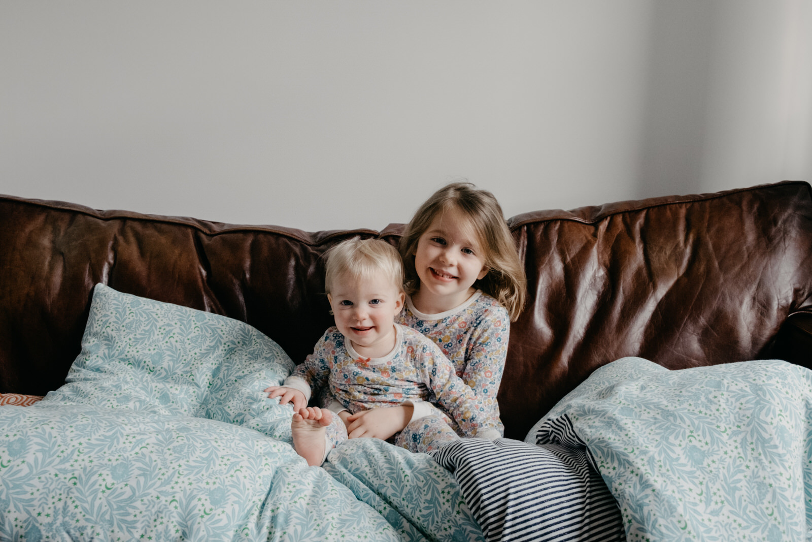 sisters in matching pyjamas sitting on couch smiling at camera