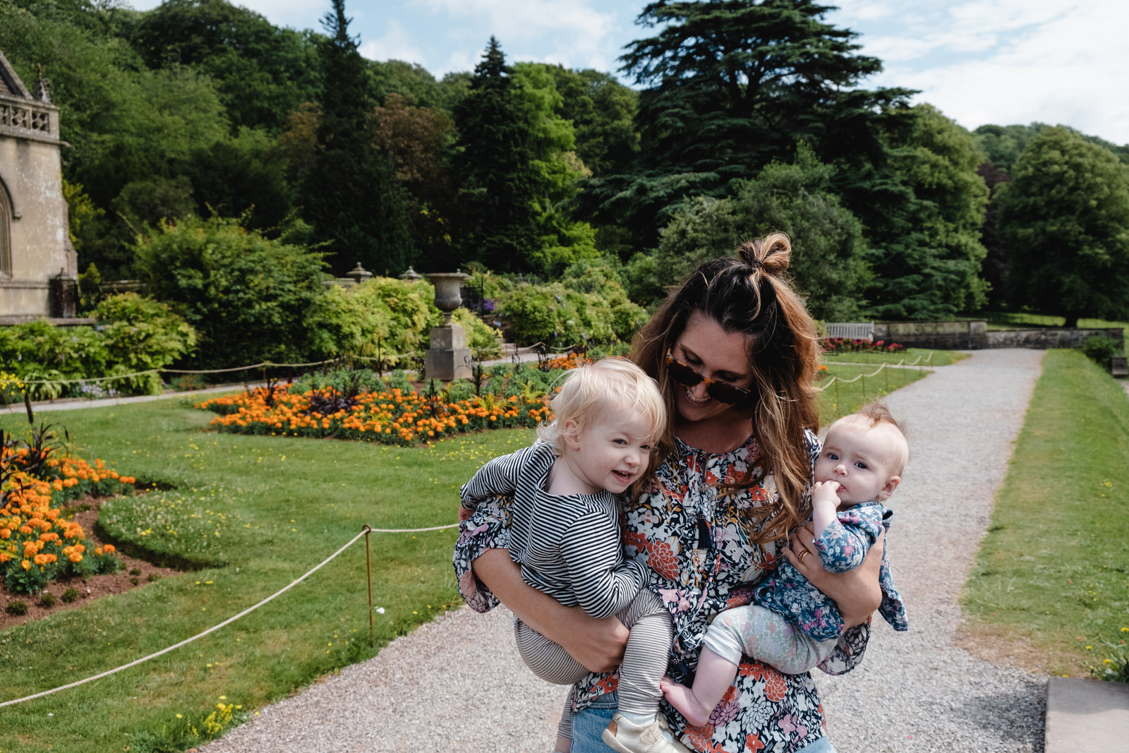 mother holding two young daughters in beatiful gardens of Tyntesfield