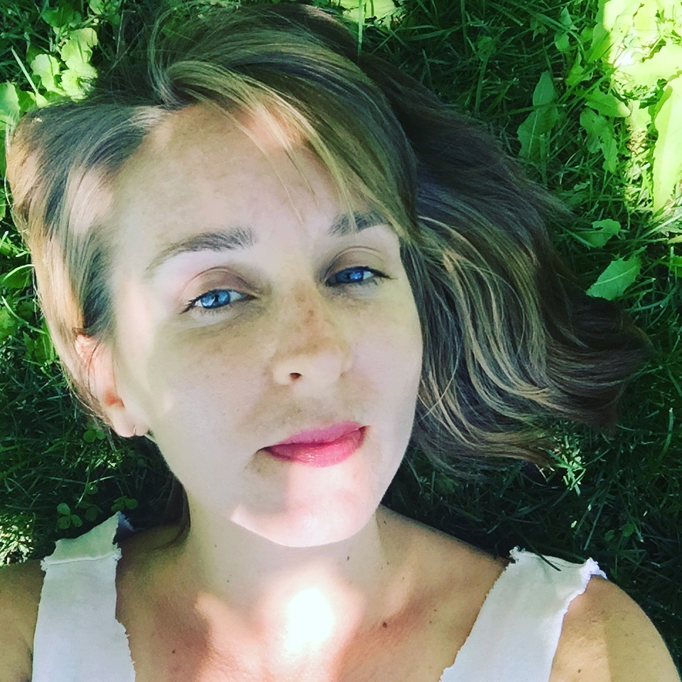beautiful woman lying on the green, summer grass, looking at the camera and taking a selfie