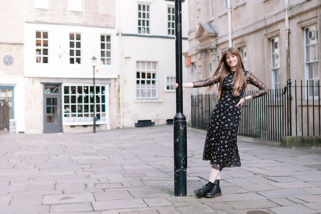 beautiful woman with long brown hair in a black dress and dr martens holding onto a lamppost in old English town