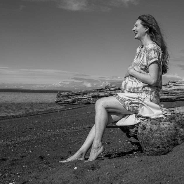Sica Schmitz heavily pregnant woman is sitting on a rock on the beach, laughing as she looks into the horizon