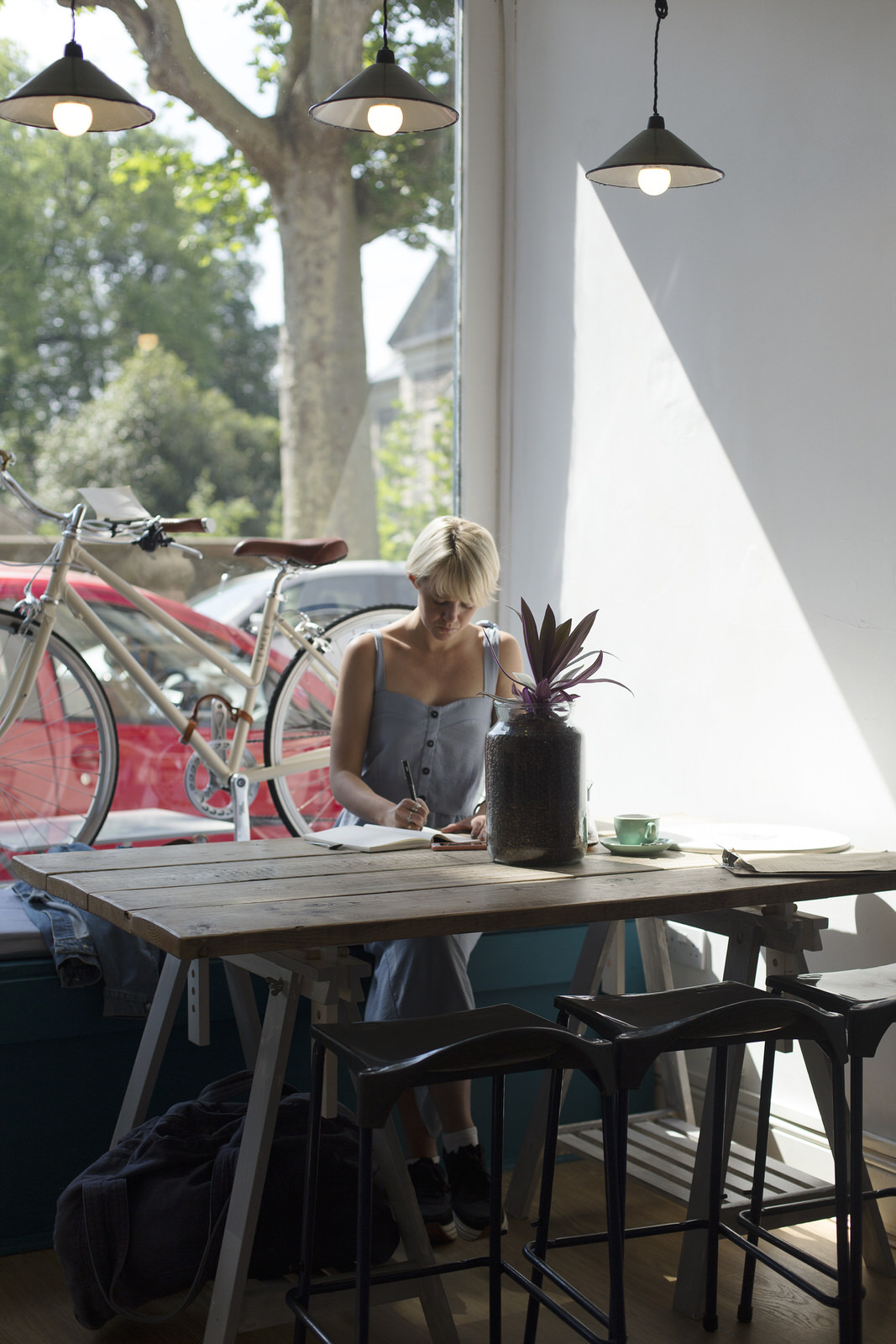 woman sitting in front of a sunny window in a cafe and writing